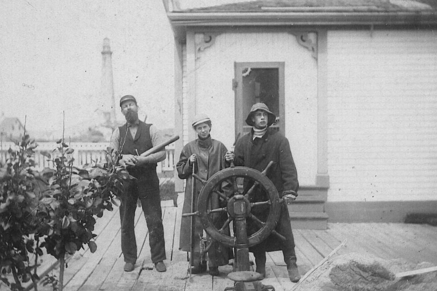 Unidentified keepers pose on porch of Principal keeper house on July 28, 1896. This may be Principal keeper Addison Franklin Tarr, with telescope, who served from 1881 to 1912.