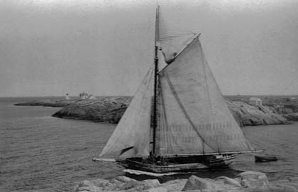 "Granite sloop Albert Baldwin sailing through the ""gap"" in 1920. Boat house on the right built in 1867 and eliminated in 1937."